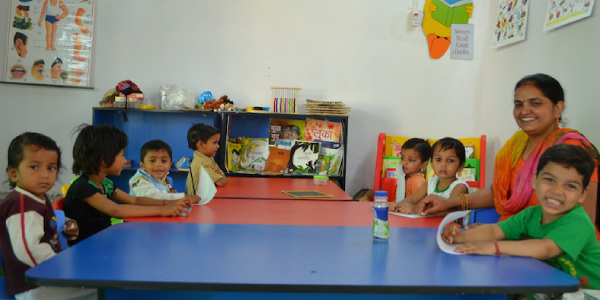 Pre-schooled Kids Sitting Around The Table With Their Teacher To Learn Emotions.