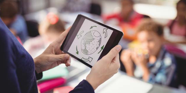 A Teacher Holding Tablet And Teaches The Kids.
