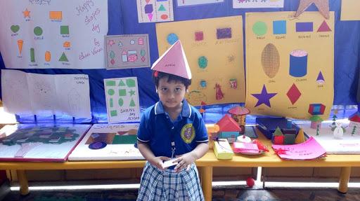 A Cute Little Girl Standing Infront Of The DIY Chart Activities.