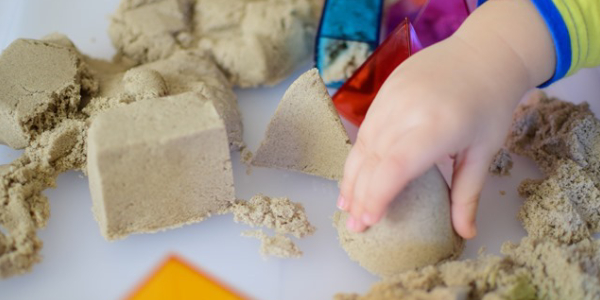 A Kid Playing With Kinetic Sand.