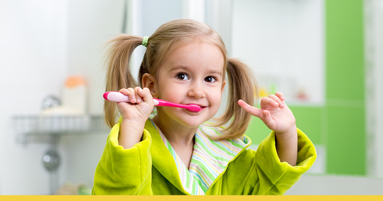A cute little girl brushing her teeth infront of the mirror in the bathroom.