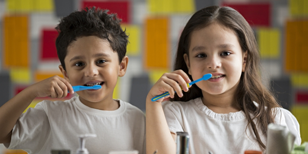 Two Cute Happy Kids Brushing Their Teeth Infront Of Mirror Representing The Healthy Teeth Concept.