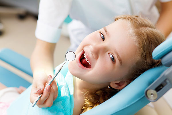 A Little Girl facing towards the camera by opening her mouth for her oral treatment Sitting in a dental clinic.